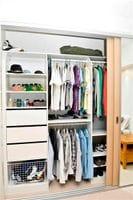 Standard wardrobe internals, open drawer fronts, slide out wire basket and sliding doors on triple track