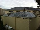 South Yarra - An external view of the closed perpendicular bi-parting skillion style retractable roof over a pool