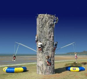 5 people rock climbing bungee wall set-up at the beach