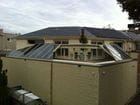 South Yarra - An external view of the open perpendicular bi-parting skillion style retractable roof over a pool