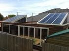 Werribee - An external view of the open bi-parting saw tooth style retractable roof over an entertaining area